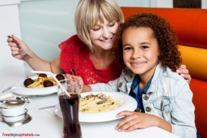 niña feliz comiendo pasta sin gluten en restaurante