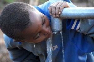 niño bebiendo agua potable de una fuente