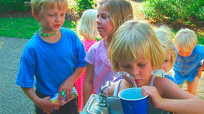 niños beben en fuente de sistema de dosificación de cloro
