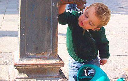 niño pequeño bebiendo agua potable de una fuente